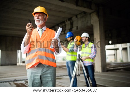 Confident team of architects and engineers working together on construction site #1463455037