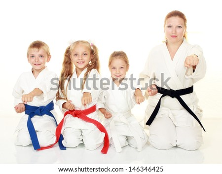 Mom with her daughter and a boy sitting with his sister in a ritual pose karate and beat his fist #146346425