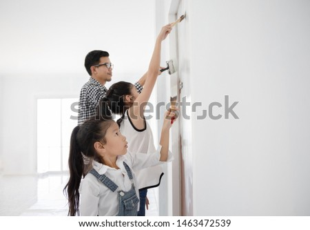 Asian little girls painting her new house with father, DIY concept #1463472539