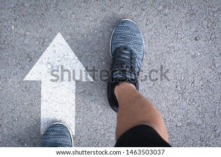 Top view of man wearing shoes choosing a way marked with white arrows. Chooses the right path concept. #1463503037