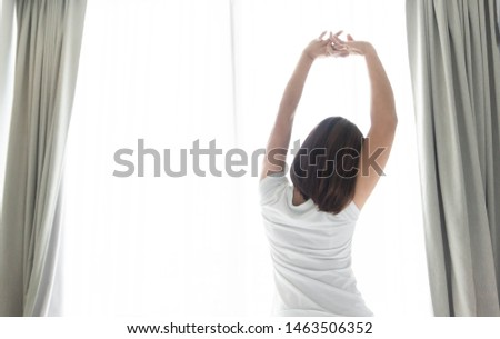 Close up woman sitting on the bed and stretching after waking up for relax in the morning with over light background #1463506352