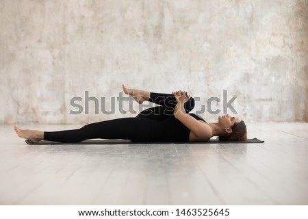 Woman wear black sport clothes lying on floor practising asana do Half Knees to Chest Pose near grunge wall beige textured background, help ease back pain, flexible body stretch for beginners concept #1463525645