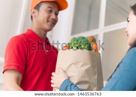 Asian delivery man in red color uniform handling bag of foods or vegetables to young beautiful female costumer in front of the house. Postman or express delivery service concept. Focus on girl eyes. #1463536763