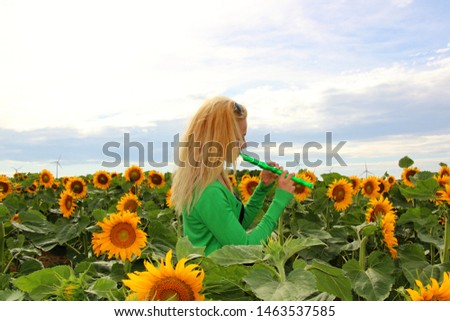 young woman standing in sunflower field and playing flute #1463537585