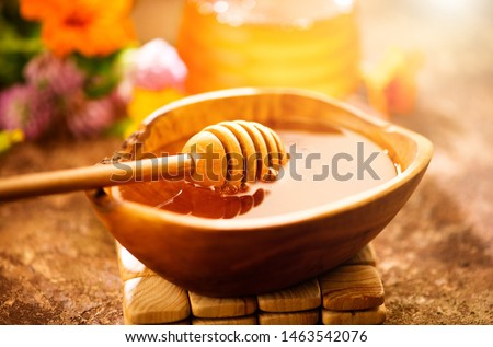 Honey dripping from honey dipper in wooden bowl.  Close-up. Healthy organic Thick honey dipping from the wooden honey spoon, closeup. Flowers and jar on the table #1463542076