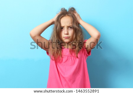 The girl is scratching her head on a colored background.