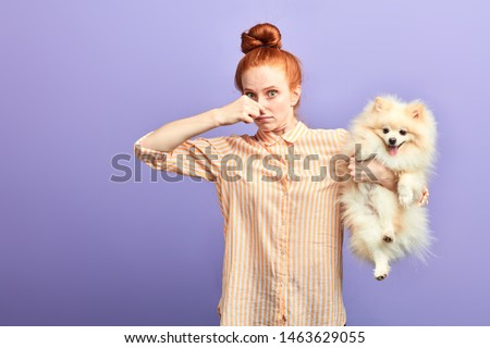 funny girl with stylish striped shirt closing her nose, as the dog is farting. close up portrait. unpredictable situation, isolated blue background, studio shot. #1463629055