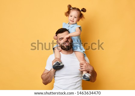 naughty girl holding her daddy's nose, display negative, angry behaviour. close up photo. isolated yellow background.father cannot manage with naughty behaviour