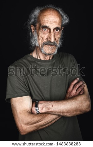 close up portrait of elderly sick man in green t-shirt with crossed arms posing to the camera in black background. studio shot.tiredness,studio shot. #1463638283