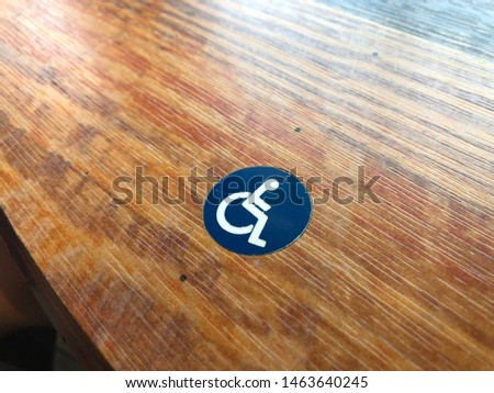Blue and White Handicapped symbol on wooden surface