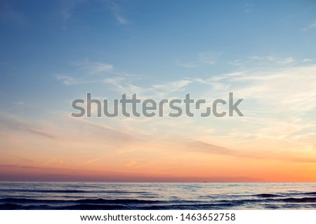 A sunset on the beach in summer. Sea and eveninig sky with clouds #1463652758