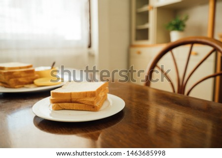 Slices of toast bread with butter on wooden table.Butter and bread for breakfast, wooden background with copy space. Morning breakfast with coffee, butter and toasts. #1463685998