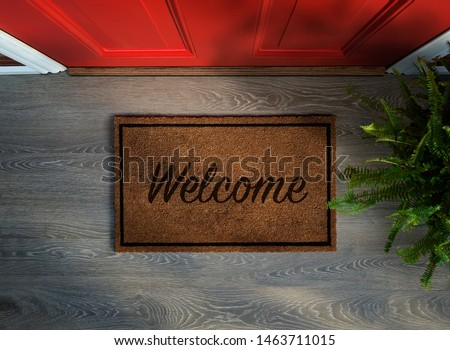 Overhead view of welcome mat outside inviting front door of house with potted fern plant Royalty-Free Stock Photo #1463711015