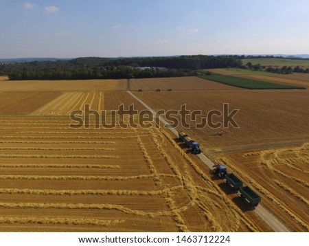 farmers harvesting a field. There is a tractor and a  combine harvester in action #1463712224
