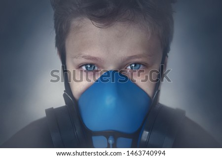 Young boy wearing gasmask, respirator portrait. Effects of worldwide air pollution, industrial influence on environment. Protection from dangerous air particles, gas, smog, transmitted diseases #1463740994