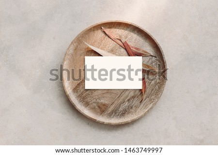 Blank white business card mockup on wooden plate. Marble backgound with dry colorful eucalyptus leaves. Modern template. Branding identity. Natural autumn, fall design. Flat lay, top view.