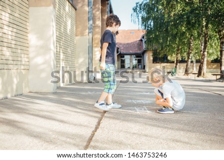 Back to school: Two happy boys drawing with chalk on asphalt #1463753246