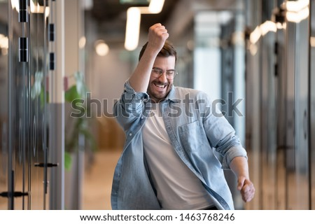 Ecstatic excited male winner dancing in office hallway laughing celebrating work achievement professional win, happy overjoyed business man enjoy victory dance euphoric about success reward promotion Royalty-Free Stock Photo #1463768246