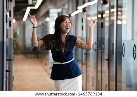 Excited funny young asian business woman celebrate success in victory dance, happy euphoric proud chinese female professional winner feel overjoyed by corporate reward standing in office corridor #1463769134