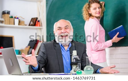 Biology science. Study biology. Biological research. Teacher and girl with notepad near chalkboard. College university education. Biologist or chemist with microscope teaching student biology. #1463769731