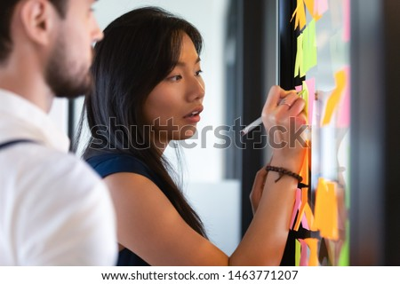 Focused asian business woman mentor coach leader writing idea or task on post it sticky notes on glass wall, serious team people developing work plan in creative corporate office at stand up meeting