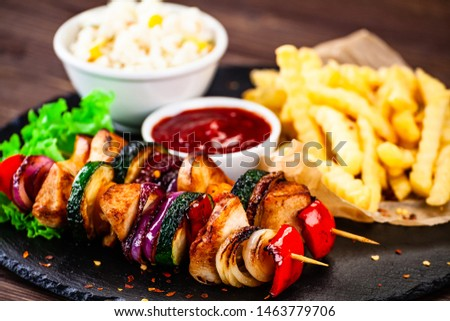 Kebabs - grilled meat with french fries and vegetables wooden background #1463779706