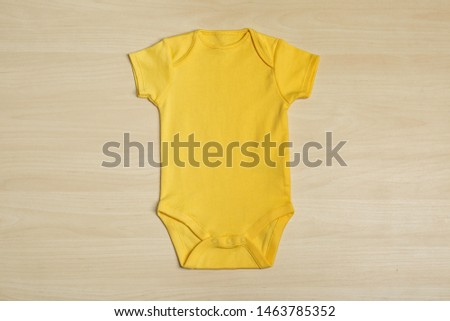Cute baby onesie on wooden background, top view #1463785352