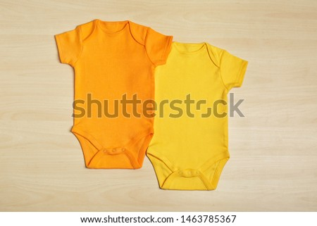 Cute baby onesies on wooden background, top view #1463785367