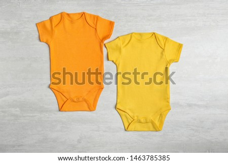 Different baby bodysuits on wooden background, top view #1463785385