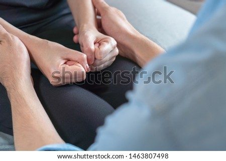 Asian woman fists both hand on legs and sit on sofa and support by man #1463807498