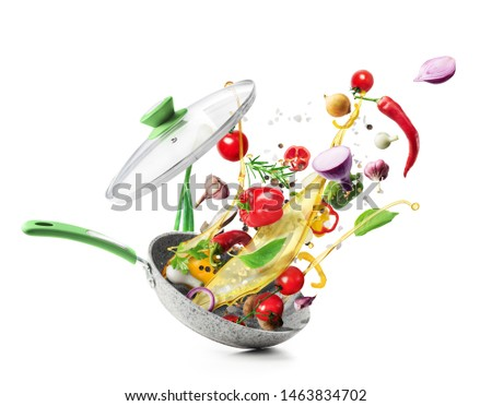 Cooking concept. Vegetables are flying out of the pan isolated on white background. Healthy food. #1463834702