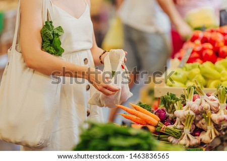 Female hands puts fruits and vegetables in cotton produce bag at food market. Reusable eco bag for shopping. Zero waste concept. #1463836565