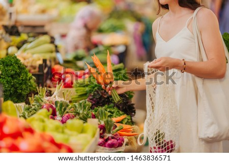 Young Woman puts fruits and vegetables in cotton produce bag at food market. Reusable eco bag for shopping. Zero waste concept. #1463836571