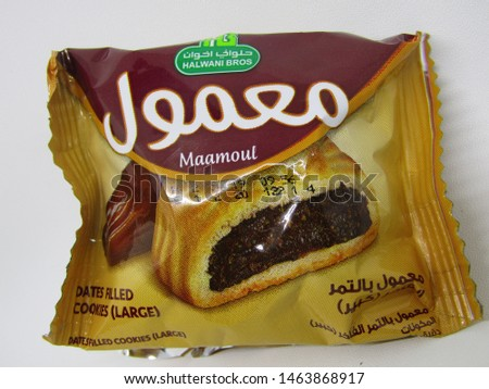 Surabaya, Indonesia - July 2019: Close up view of Eat maamoul dates filled cookies in brown yellow color package. Premium date rolls or kue kurma snack filling inside. Sweet cake small little large #1463868917