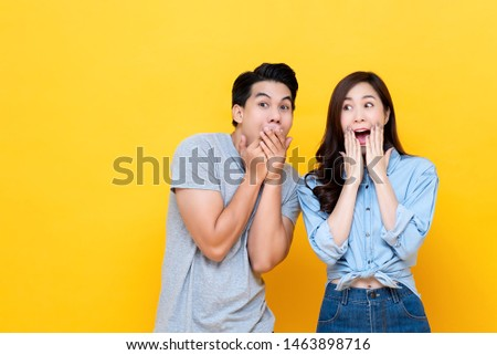 Cheerful young Asian couple being excited with fabulous secret isolated on yellow studio background