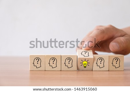 Business concept of creative idea and innovation. Hand flip over wooden cube block with light bulb icon (new idea) and head human symbol have no idea. #1463915060