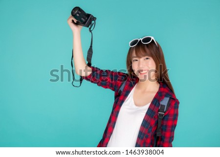 Beautiful young asian woman cheerful and enjoy travel trip summer isolated on blue background, asia girl having activity hobby take a photo holding camera, tourist journey in vacation and holiday.