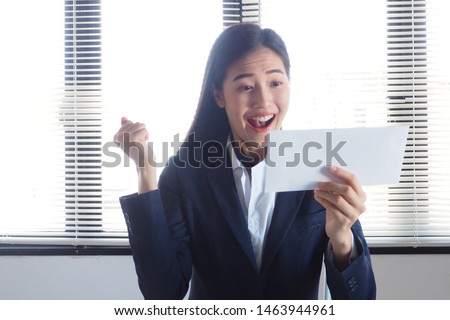 Young active Asian woman is excited with her happy face smiling and raising her hand up when she notices about getting promoted at work because of her good performance to be the best employee #1463944961