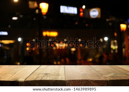 background Image of wooden table in front of abstract blurred restaurant lights #1463989895