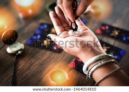 Fortune teller reading fortune lines on hand Palmistry Psychic readings and clairvoyance hands concept with Tarot cards divination / Palm reading Magic Spiritual and Horoscopes Occult Royalty-Free Stock Photo #1464014810