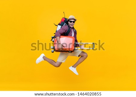 Excited happy young Asian man tourist with luggage jumping isolated on yellow studio background Royalty-Free Stock Photo #1464020855