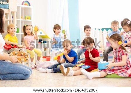 Group of kindergarten children play with musical toys. Early musical education in day care centre #1464032807