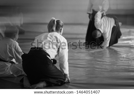 Aikido training. Black and white image. The teacher shows reception.  Traditional form of clothing in Aikido. Background image. Photo from the back. No faces and recognizable elements! Royalty-Free Stock Photo #1464051407