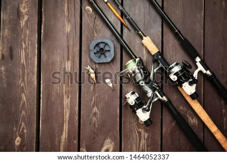 Fishing rods and reels on wooden background with text space #1464052337