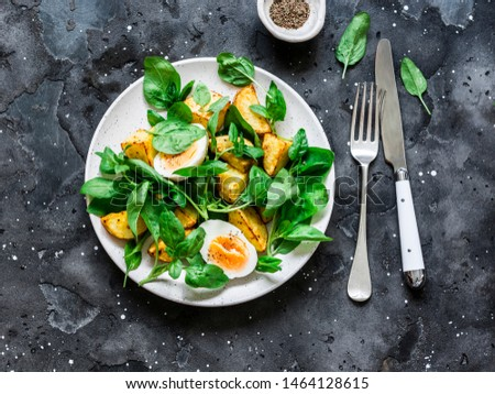Baked potato, boiled egg and spinach salad on dark background, top view #1464128615