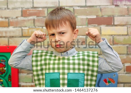 Chisinau, Republic of Moldova - July 15, 2019: portrait of a cute little boy. Showing his muscles. Horizontally framed shot. #1464137276