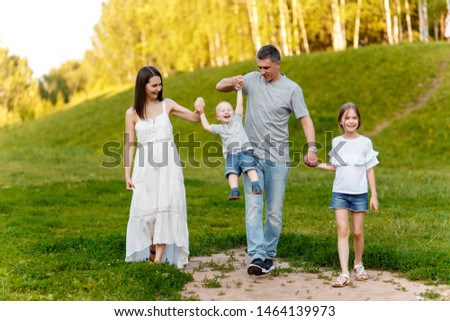 Mom, dad, son and daughter walk in the park at the weekend holding hands. Happy family in nature. fun big family in the forest. #1464139973