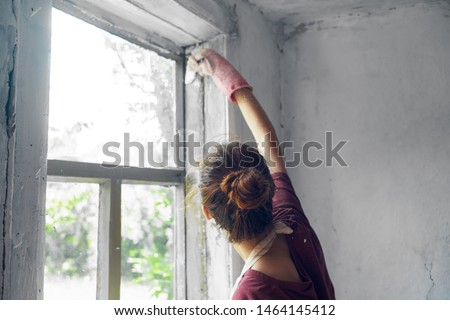 woman paints wooden windows in white #1464145412