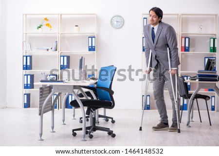 Leg injured male employee working in the office  #1464148532