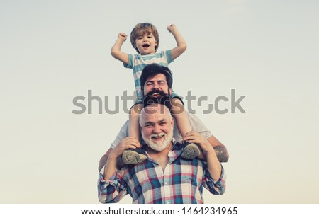 Excited. Father and son playing outdoors. Happy smiling boy on shoulder dad looking at camera. Happy family. Three men generation #1464234965